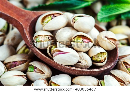 Pistachios in a wooden spoon. Selective focus - stock photo