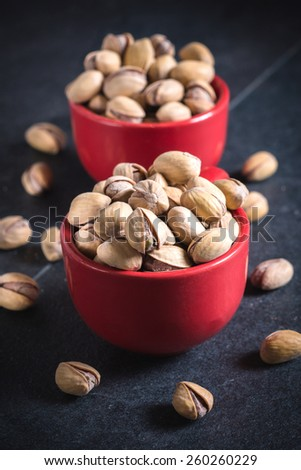 Pistachios in red coffee cups,selective focus - stock photo