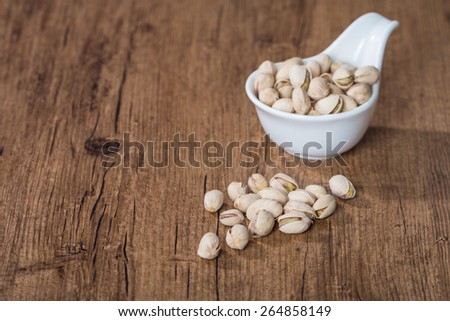 Pistachios in white bowl on wooden background - stock photo