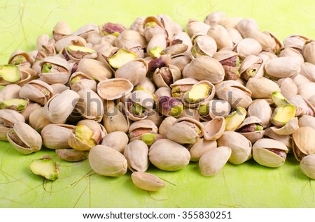 Pistachios on bright green background.