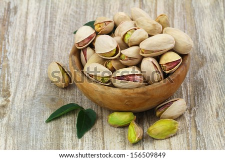 Pistachios with and without shell in wooden bowl with copy space  - stock photo
