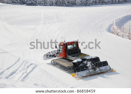 Piste preparation vehicle moving slowly over piste, making it even again - stock photo
