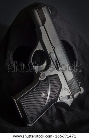 Pistol and mask of a thief over black background - stock photo