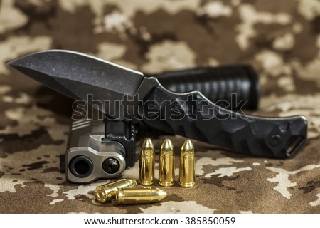 Pistol, cartridges and a knife - stock photo