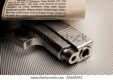 pistol concealed with a newspaper - stock photo