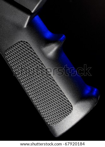 Pistol grip on an assault rifle with a blue gel at the side - stock photo