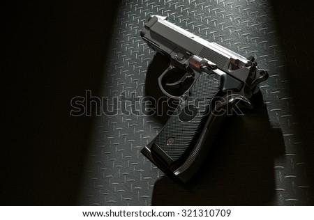 Pistol on the floor in a light room 3d rendering - stock photo