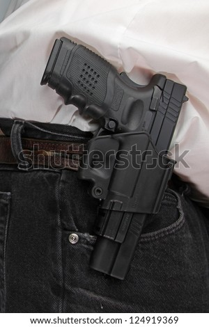 Pistol Packing/close up of holstered handgun against plain white shirt & black denim - stock photo