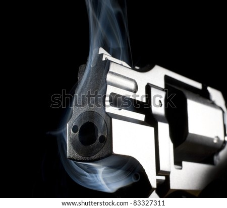 Pistol that has smoke around its muzzle and frame - stock photo