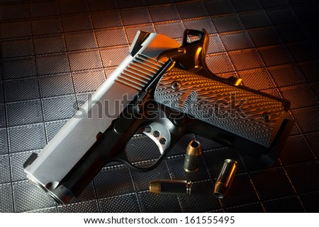 Pistol with cartridges on a textured background and orange gel - stock photo