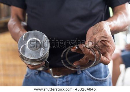 Piston and cylinder ring in car mechanic hands  - stock photo