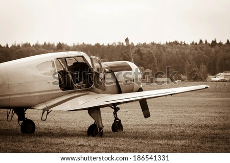 piston training aircraft on the ground with an open door to the cockpit - stock photo