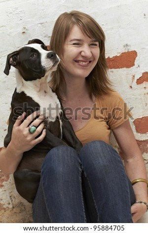 Pit Bull puppy sitting on lap of smiling dog owner - stock photo