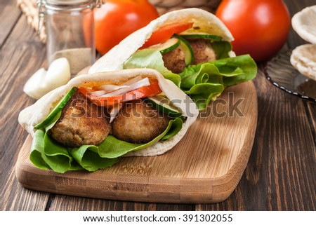 Pita bread with falafel and fresh vegetables on wooden table - stock photo