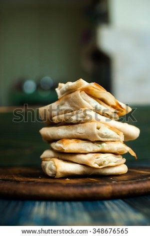 Pita bread with greens and cheese on a wooden board - stock photo