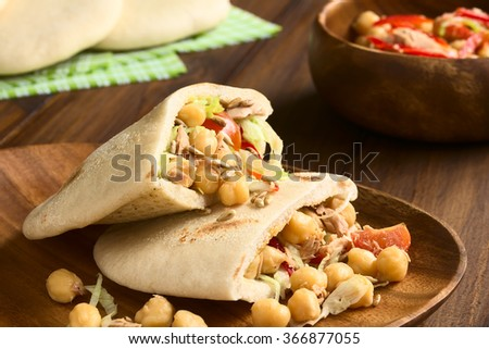 Pita sandwich stuffed with chickpea, tuna, lettuce, pepper, cherry tomato, roasted sunflower seeds, photographed with natural light (Selective Focus, Focus one third into the stuffing of upper pita)