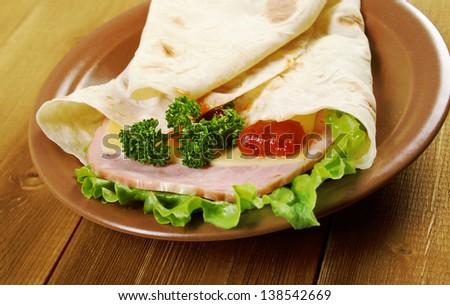 Pita Sandwich with cheese,ham,parsley,and tomato sauce - stock photo