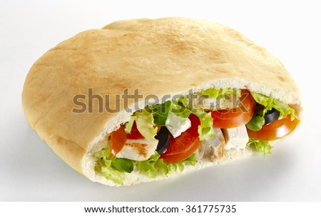 Pita sandwich with lettuce, feta cheese, chicken fillet, tomato and black olive, on a white background - stock photo