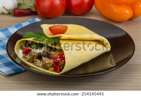Pita with roasted aubergine in board on wooden background