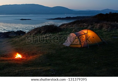 Pitched nylon tent erected for camping vacation near the beach and coast - stock photo