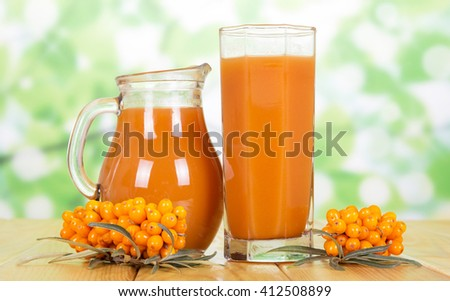 Pitcher and a glass of juice from the berries of sea-buckthorn berries on a green abstract background.