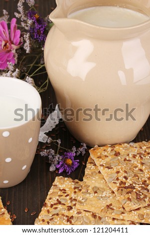 Pitcher and cup of milk with cookies on wooden table close-up - stock photo