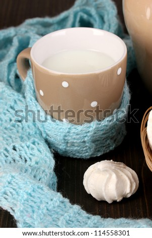 Pitcher and cup of milk with meringues on wooden table close-up - stock photo