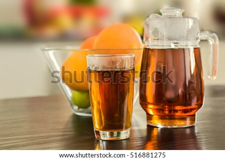 Pitcher and glass of hot black tea with bowl of fruits on the background.