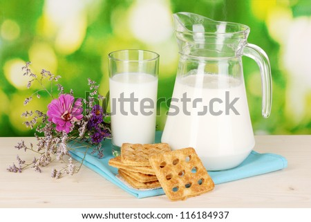 Pitcher and glass of milk with cookies on wooden table on natural background