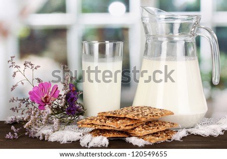 Pitcher and glass of milk with cookies on wooden table on window background - stock photo