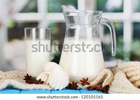 Pitcher and glass of milk with meringues on crewnecks knitwear on wooden table on window background - stock photo
