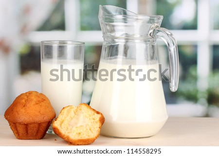 Pitcher and glass of milk with muffins on wooden table on window background - stock photo