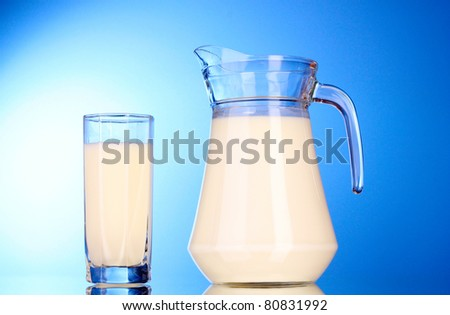 Pitcher and Glass with milk on blue background - stock photo