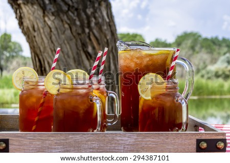 Pitcher and mason jar mugs filled with iced tea and lemons sitting on picnic table with red checked tablecloth - stock photo