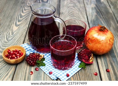 Pitcher and Two glasses of pomegranate juice with fresh fruits on wooden table - stock photo