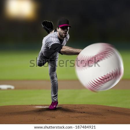 Pitcher Baseball Player on a Pink Uniform on baseball Stadium. - stock photo