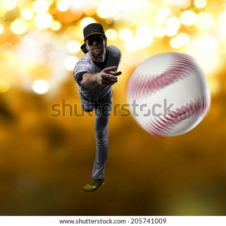 Pitcher Baseball Player on a yellow Uniform on yellow lights background.