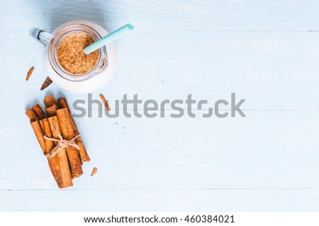 Pitcher glass of milk with cinnamon on a blue wooden background, instagram filter, space for text - stock photo
