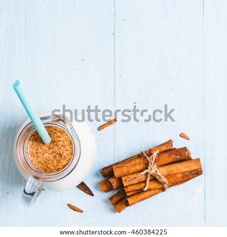 Pitcher glass of milk with cinnamon on a blue wooden background, instagram filter space for text - stock photo