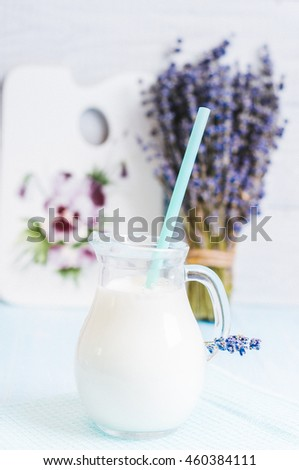 Pitcher glass of milk with lavender and cocktail tube on a blue wooden background instagram filter - stock photo