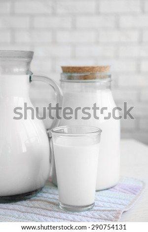 Pitcher, jar and glass of milk on wooden table, on bricks wall background - stock photo