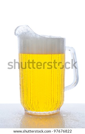 Pitcher of beer on a wet bar counter top. Vertical format over white. - stock photo