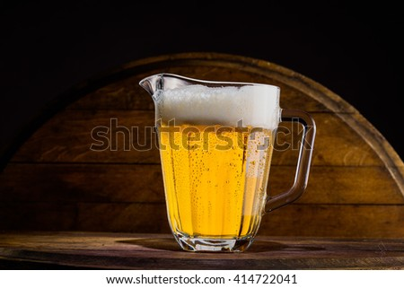Pitcher of beer on wooden background - stock photo