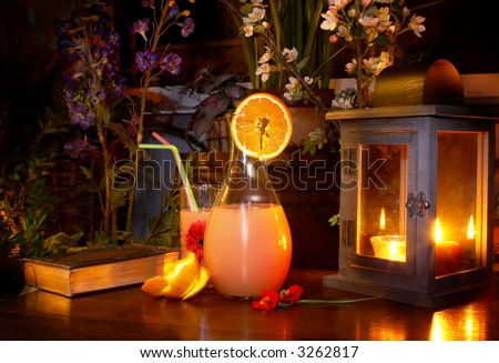 Pitcher of lemonade on a wooden garden table, a night shot, painted with light