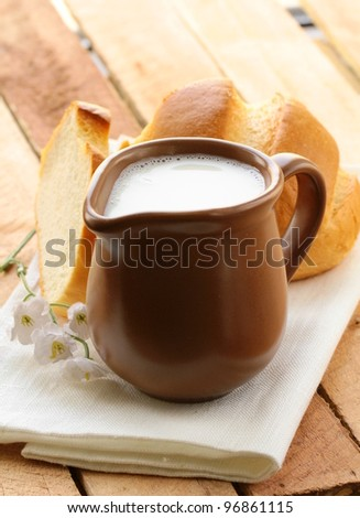 pitcher of milk on a wooden table, rustic still life - stock photo