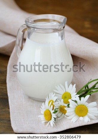 pitcher of milk on a wooden table wish daisy , rustic still life - stock photo
