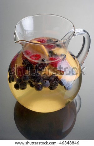 Pitcher of white wine sangria on grey background with reflection - stock photo