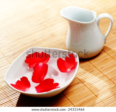 Pitcher, water, and floating rose petals - stock photo