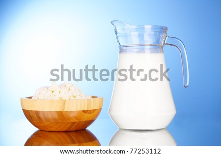 Pitcher with milk and cottage cheese on blue background with reflection