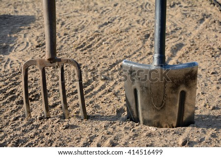 Pitchfork and spade stuck in the ground closeup. - stock photo